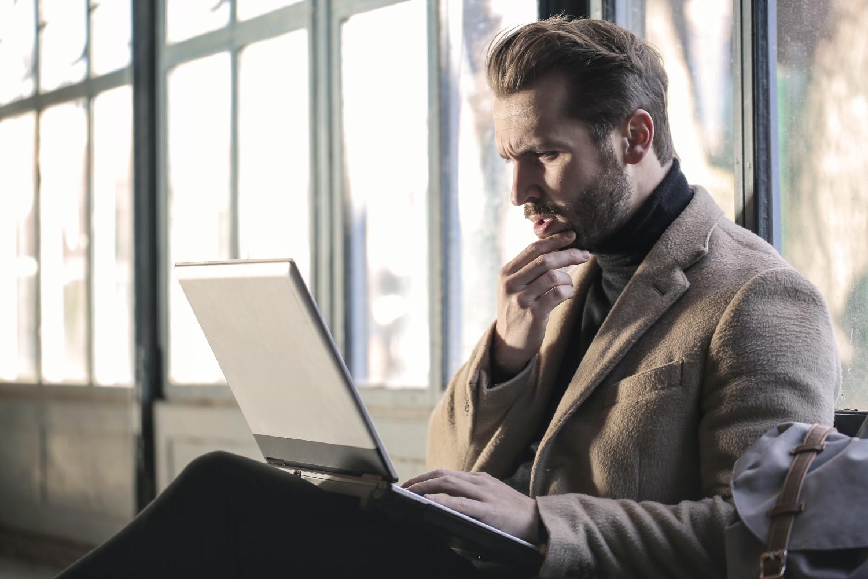 Homme qui s'interroge devant un ordinateur portable