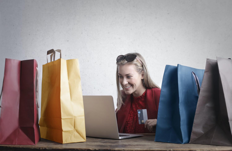 femme qui fait des achats en ligne avec sa carte de credit. Elle est entourée de sacs de shopping de couleur
